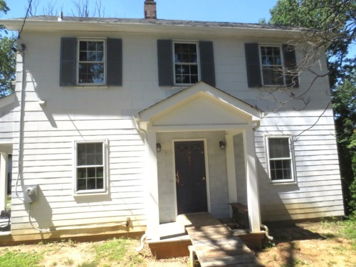 The front of the house needs work: painted siding, painted shutters, painted doors, and landscaping.