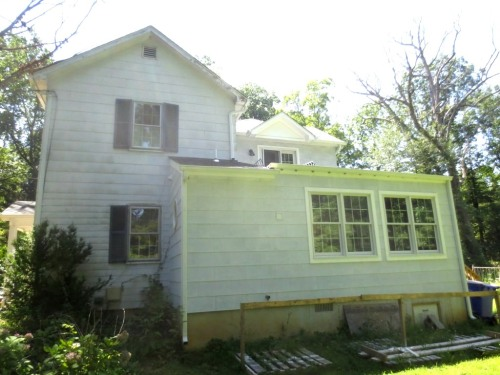 The original trim on the eaves and windows of the house needs to be scraped, primed, and painted.