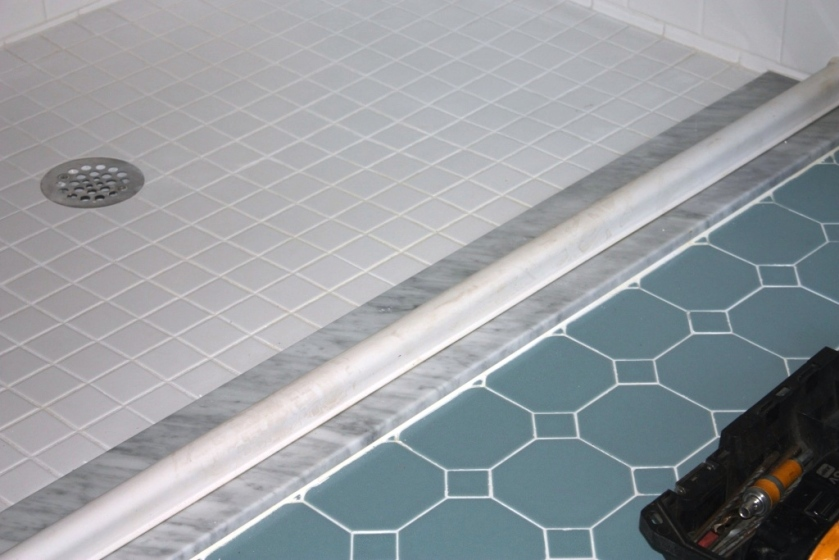 A newly tiled shower worked into an old bathroom with a minimal threshold.