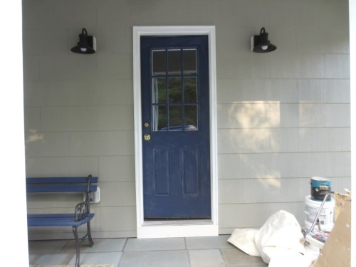 The dark fixtures and electric outlet (behind the bench) on the side porch were mounted on white plates.