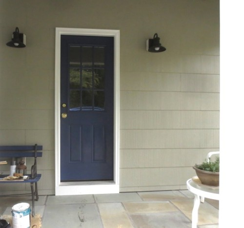 The side porch is painted with the new house color, new door color, and bright white trim.