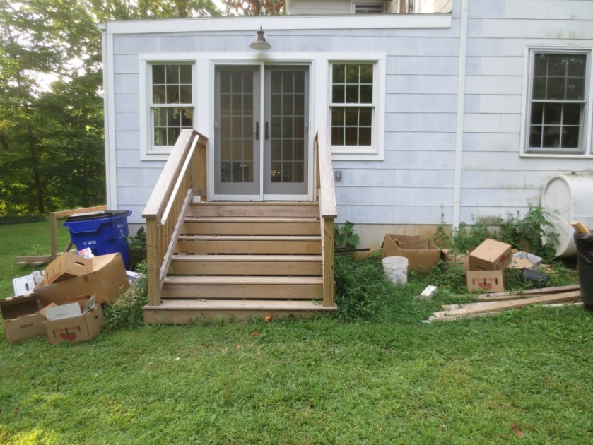Building supplies and cardboard boxes are cluttering up the area around the back steps.