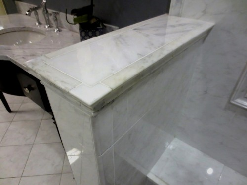 The knee wall could be capped something like this -- one piece of marble with an applied edging.