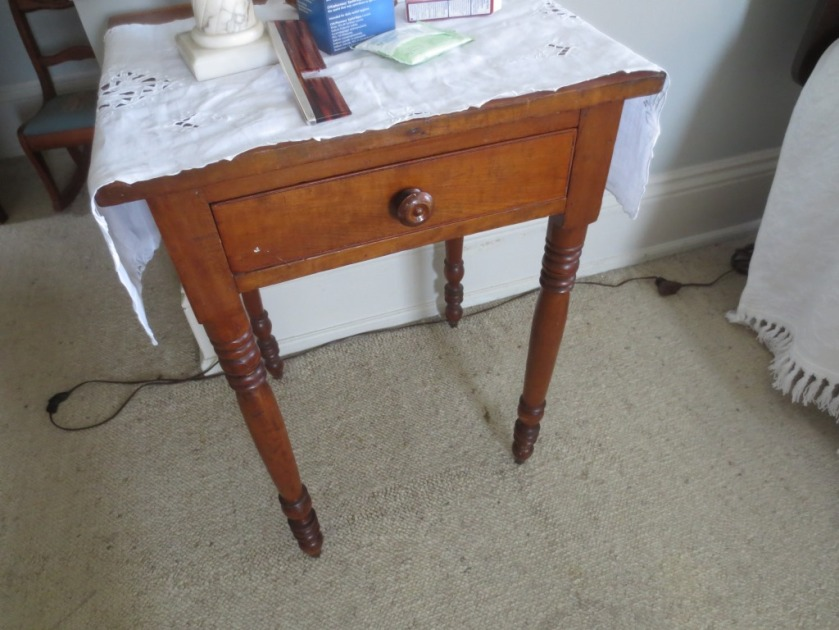 A dresser scarf is used to protect the top of this old table.