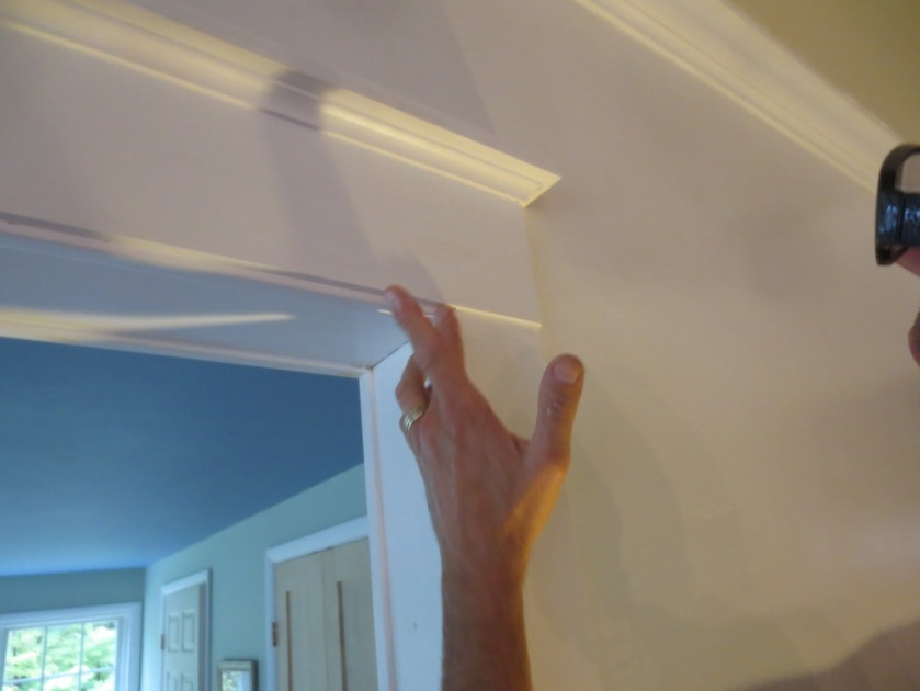 Charlie smooths the caulk with a wet finger.