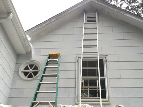 The eaves have been scraped and caulked. See the improvement below after primer and paint.