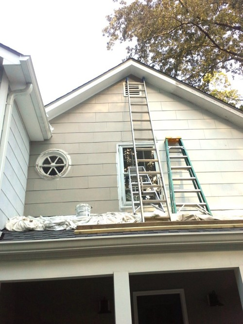The shingles and eaves have been caulked and painted to the left of the tall ladder.