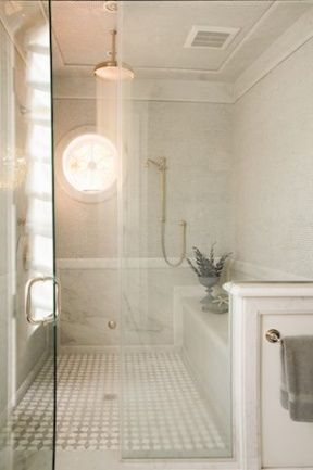 This shower my inspiration for the master shower -- ceiling rainhead, round window, marble tile, bench, handheld shower.