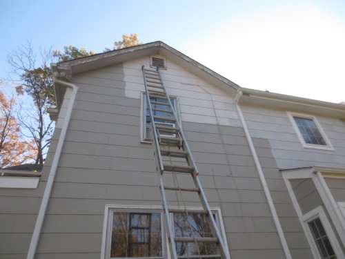 A 24-foot extension ladder reaches to the highest points of the houses.
