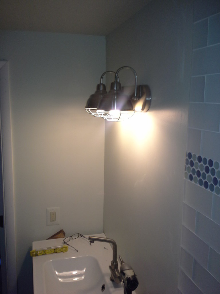 Both the lighting fixture and the sink are installed in the conservatory bathroom.