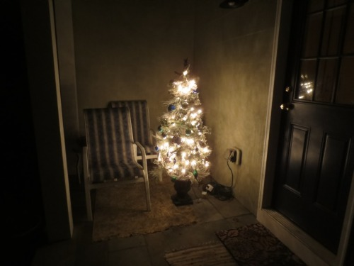 An artificial tree on the side porch.