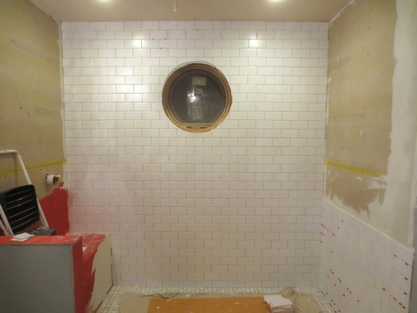 """In the master shower the floor is white marble and the walls are """"ice white"""" ceramic."""