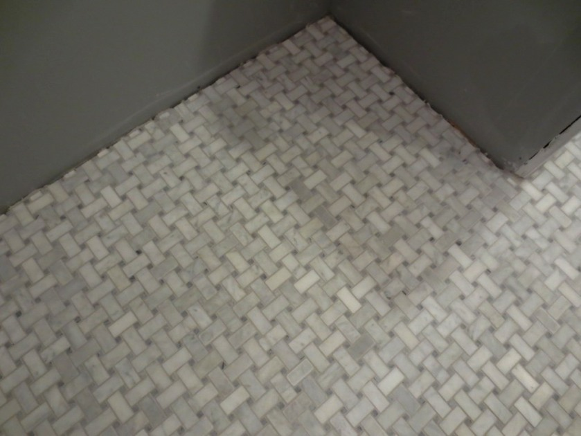 Marble basketweave tile with warm grey grout is on the floor..