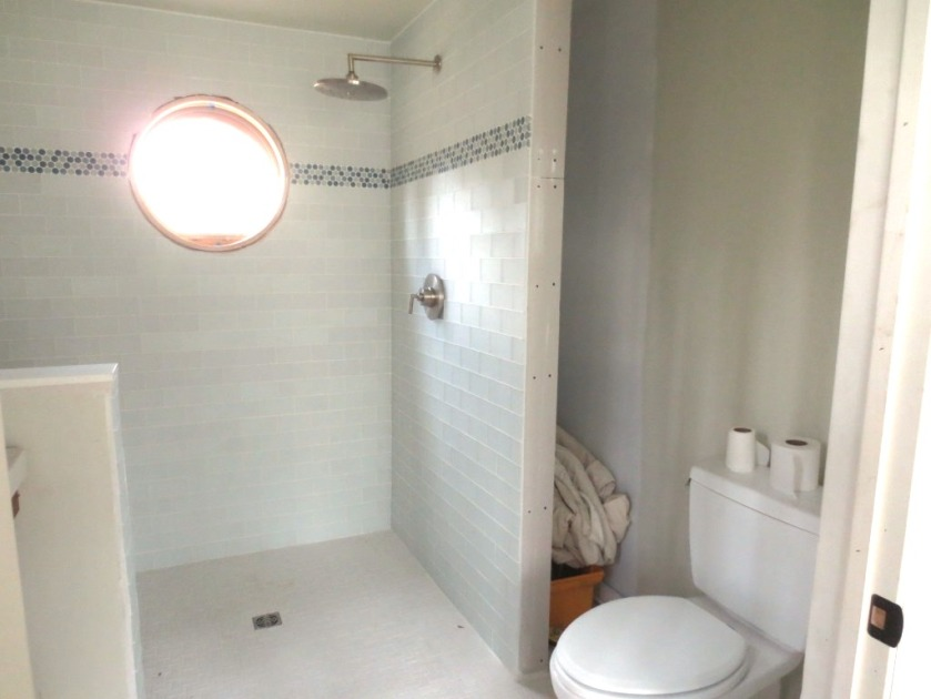 The area to the left of the toilet, behind the shower, will be covered with shallow shelves made from vintage wood.