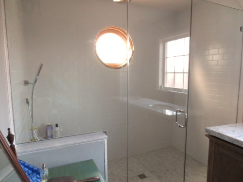 The shower glass makes the bathroom brighter because it is so reflective. (There is only a round window in the shower, the other one is a reflection.)