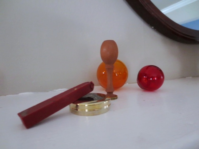 Sealing wax, a seal, and a tin of gold ink.
