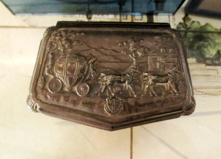 An old silver box with a repousséd horse-drawn carriage.