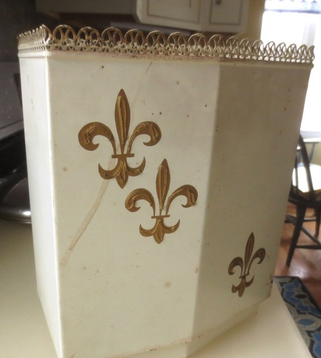 Vintage metal wastebasket with a weighted bottom.