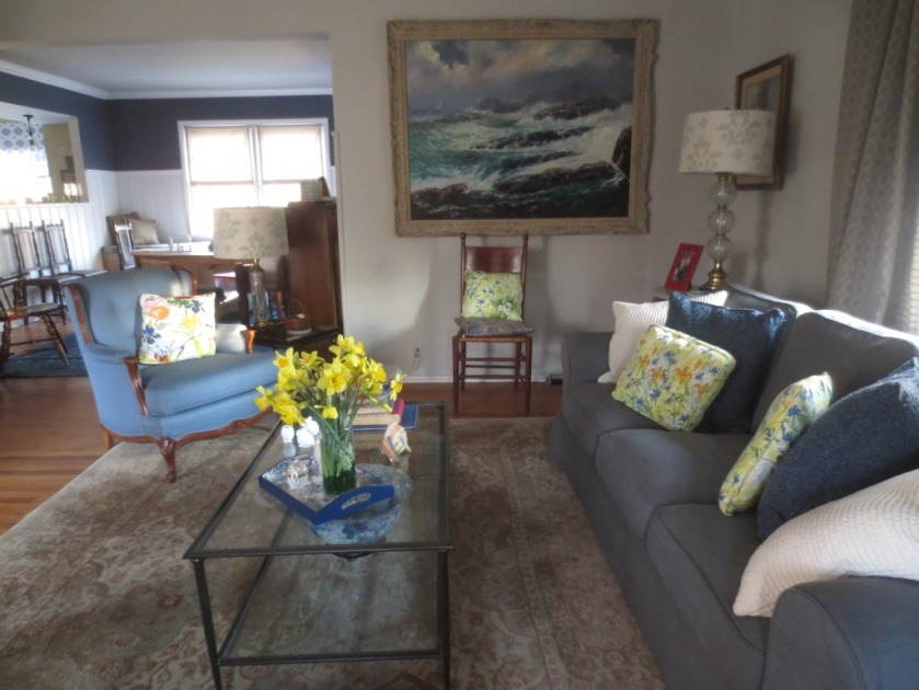 The mostly grey/blue living room is brightened by flowery cushions and real flowers.
