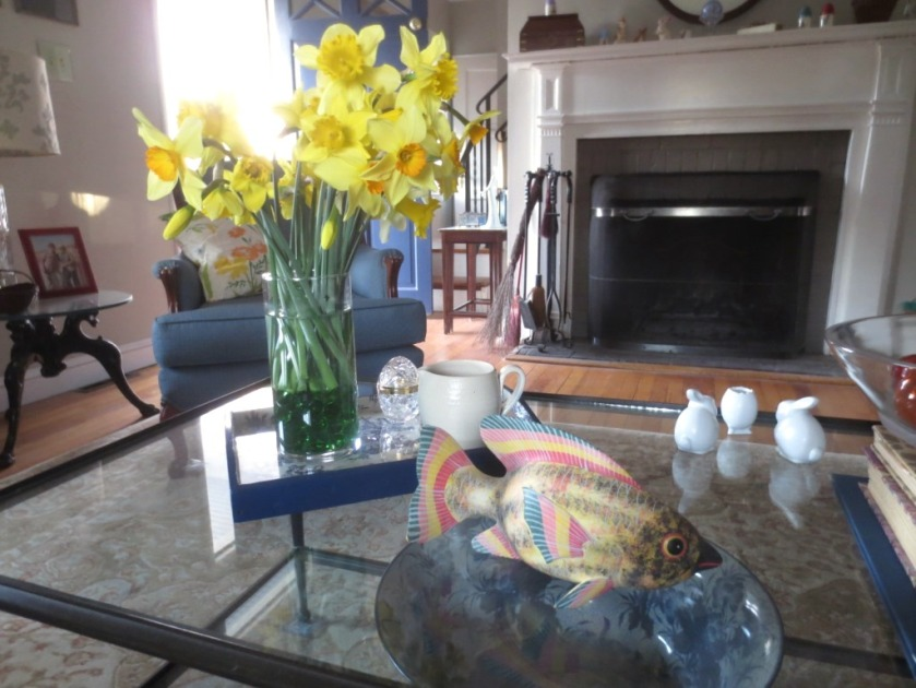 A vase of yellow jonquils are in a clear vase with green glass pebbles to raise the height if the flowers.