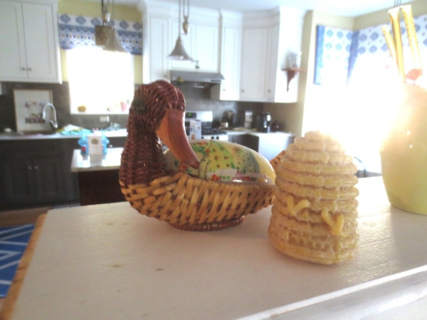 Duck basket and beeswax bee skep are on the ledge between the kitchen and dining room.