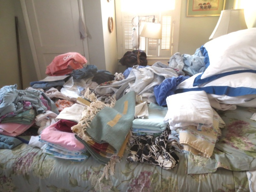 The bed is cluttered with mostly sheets and towels.