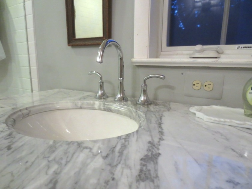 The vanity top is white marble with grey veining.