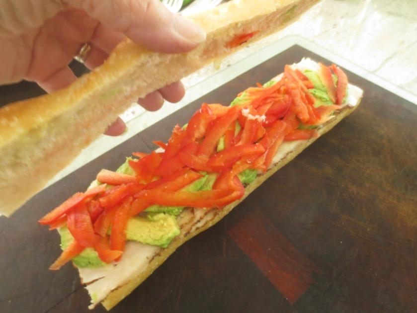 Grating the red bell pepper makes the texture more pleasant in the sandwich than chopping it.