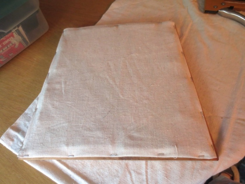 Turn under the raw edges of the muslin and staple over the webbing.