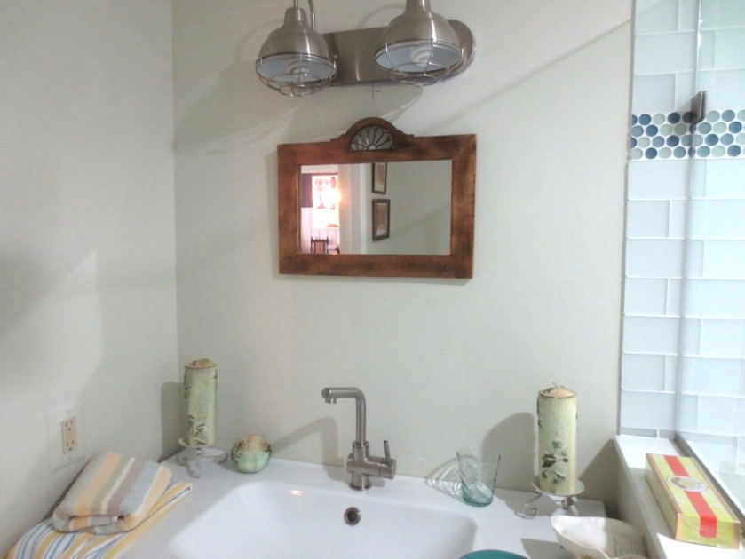 The over-sink mirror co-ordinates with the rustic look in the bathroom.