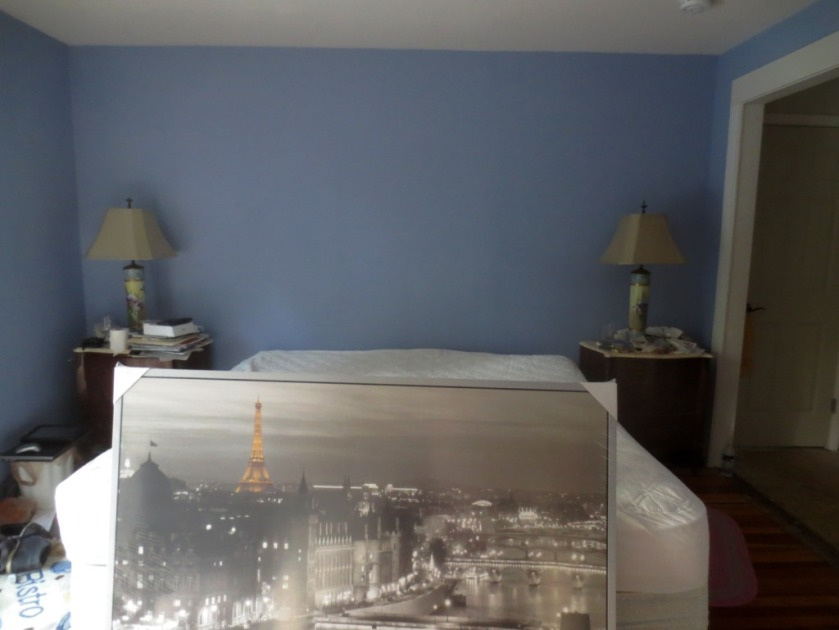 he bright blue of our bedroom walls are relieved with a wall of grey shelves and a large black and white photo.