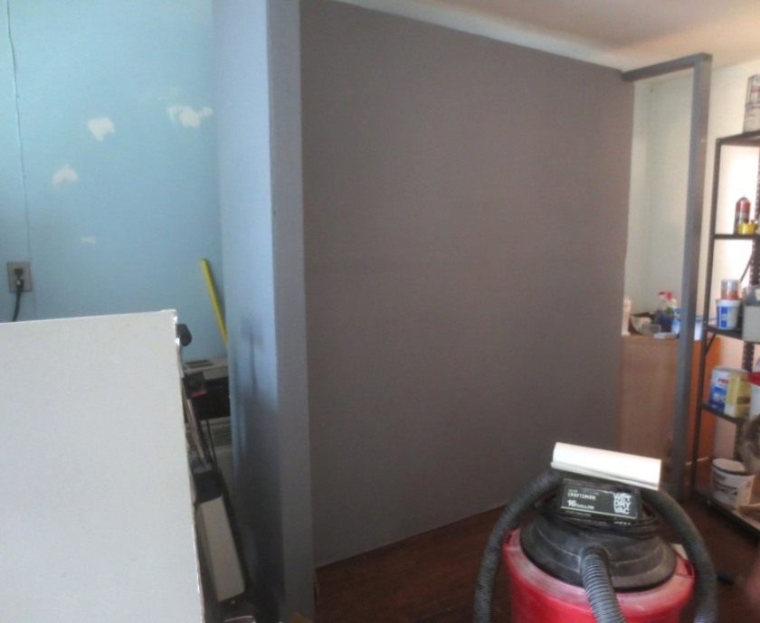 "Both sides of the floating wall are faced with drywall and painted ""Templeton Grey""."