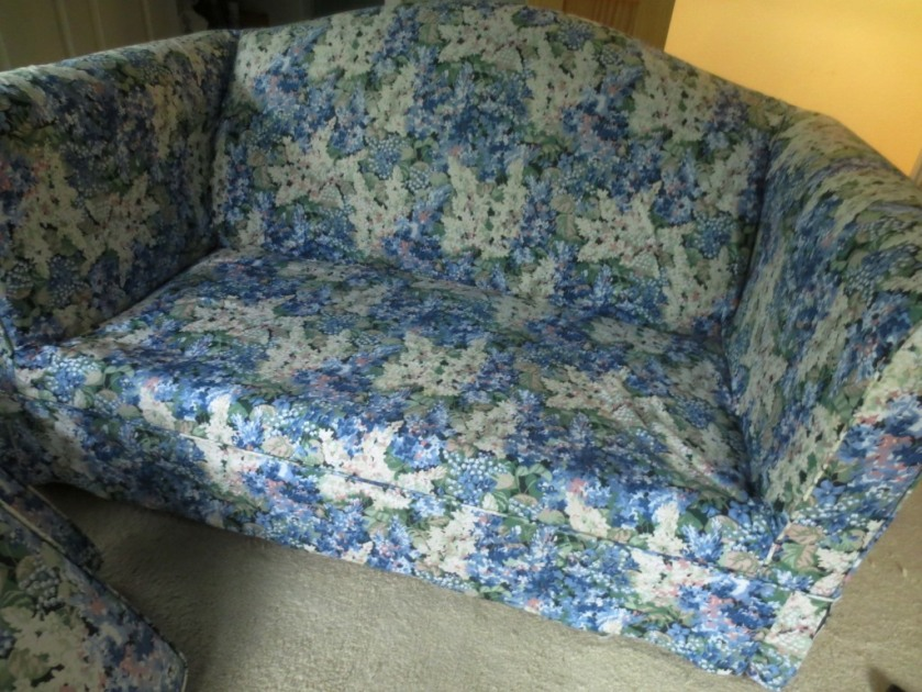 The slipcover gets tucked into the crevasses of the loveseat before returning the cushions.