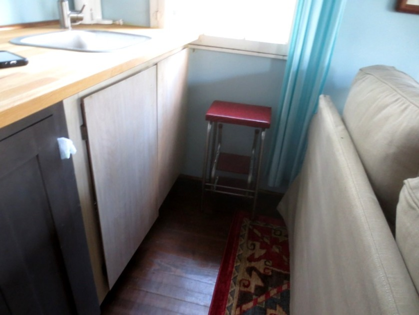 A ruby red vintage step stool fits in the corner of the mini kitchen.