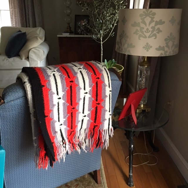 I found both red, white, black and grey afghans and hung one on the back of the matching blue living room chairs.
