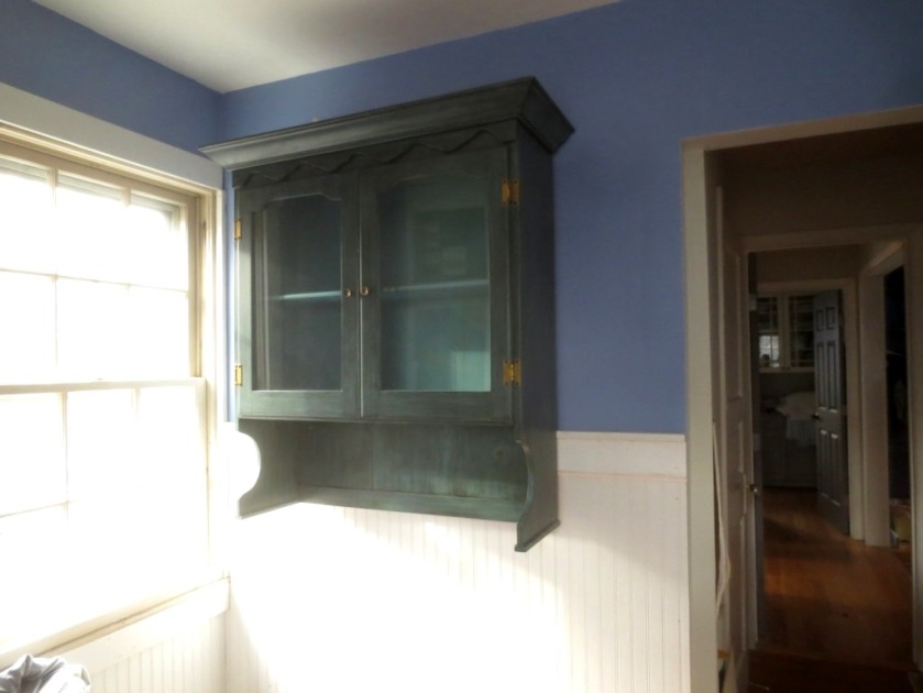 The cabinet is securely hanging on the wall in front of the trim.