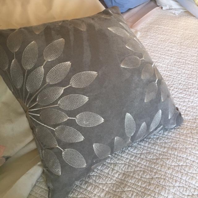 A very elegant embroidered grey velvet pillow.